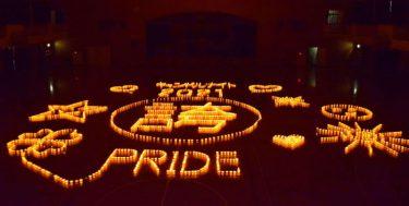 夕闇の体育館に浮かんだ大きな「誇」 2300個の灯で描いた沖縄の親たちの思い
